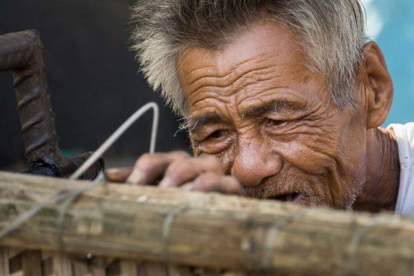 Un vieil homme vietnamien réparant des bateaux