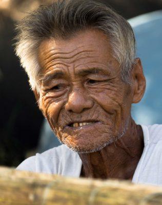 Un vieil homme vietnamien réparant des beateaux