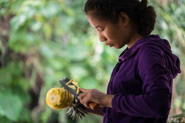 Portrait d'une jeune fille vietnamienne découpant un ananas